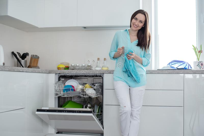 Χαμογελώντας γυναίκα στα άσπρα τζιν και ένα τυρκουάζ πουκάμισο με ένα φλυτζάνι και μια πετσέτα στα χέρια της, που στέκονται δίπλα στοκ φωτογραφία με δικαίωμα ελεύθερης χρήσης