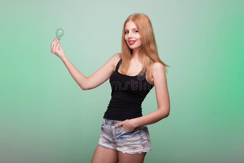Χαμογελώντας γυναίκα στα κοντά τζιν που κρατά μια λάμπα φωτός στα χέρια στοκ εικόνες με δικαίωμα ελεύθερης χρήσης
