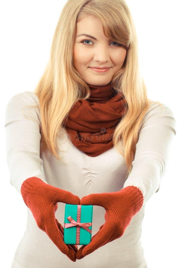 Χαμογελώντας γυναίκα στα μάλλινα γάντια με το τυλιγμένο δώρο για τα Χριστούγεννα ή άλλο εορτασμό στοκ φωτογραφία με δικαίωμα ελεύθερης χρήσης