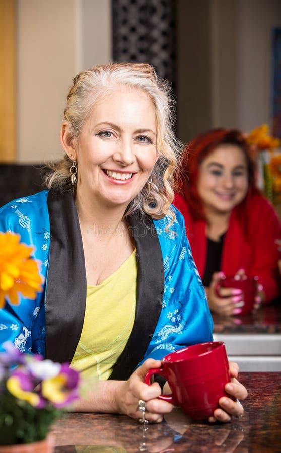 Χαμογελώντας γυναίκα στην κουζίνα στην τήβεννο στοκ εικόνα με δικαίωμα ελεύθερης χρήσης