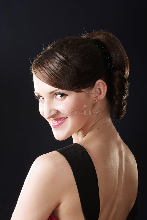 Χαμογελώντας γυναίκα στις κόκκινες στροφές φορεμάτων στοκ φωτογραφίες