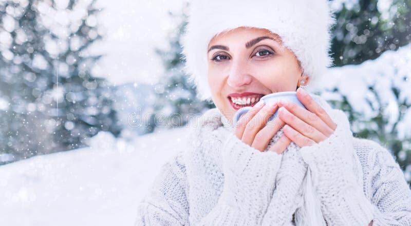 Χαμογελώντας γυναίκα στο άνετο knitwear και γουνών καπέλο με το φλυτζάνι του ζεστού ποτού στοκ εικόνα