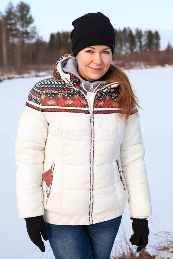 Χαμογελώντας γυναίκα στο θερμά σακάκι, το καπέλο και τα γάντια που στέκονται κοντά στην παγωμένη λίμνη στη χειμερινή εποχή στοκ φωτογραφίες