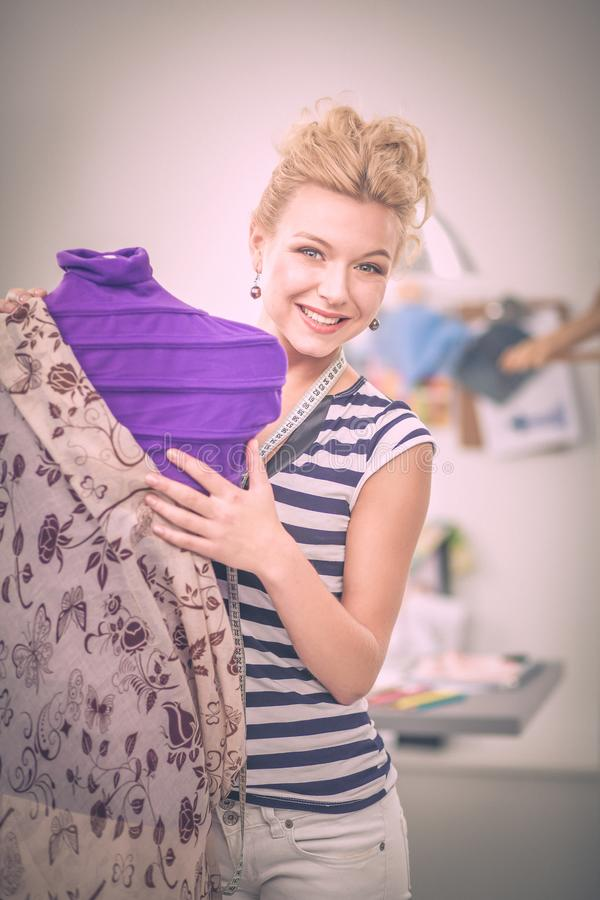 Χαμογελώντας γυναίκα σχεδιαστών μόδας που στέκεται κοντά στο μανεκέν στην αρχή στοκ φωτογραφίες με δικαίωμα ελεύθερης χρήσης