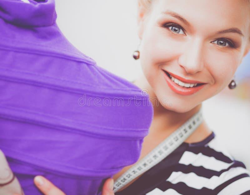 Χαμογελώντας γυναίκα σχεδιαστών μόδας που στέκεται κοντά στο μανεκέν στην αρχή στοκ εικόνα
