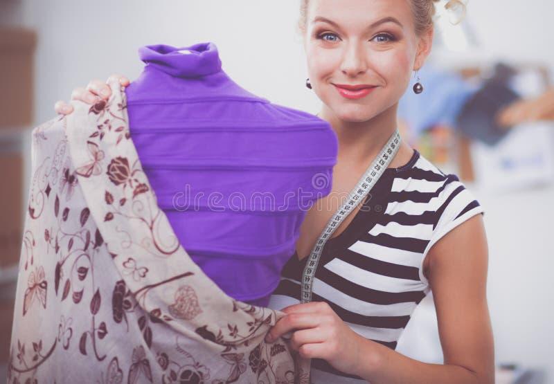 Χαμογελώντας γυναίκα σχεδιαστών μόδας που στέκεται κοντά στο μανεκέν στην αρχή στοκ φωτογραφίες