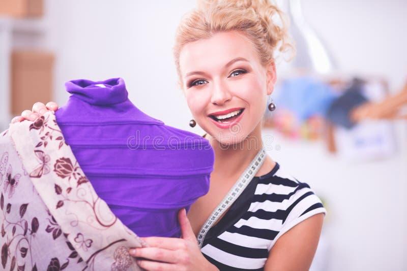 Χαμογελώντας γυναίκα σχεδιαστών μόδας που στέκεται κοντά στο μανεκέν στην αρχή στοκ εικόνες με δικαίωμα ελεύθερης χρήσης
