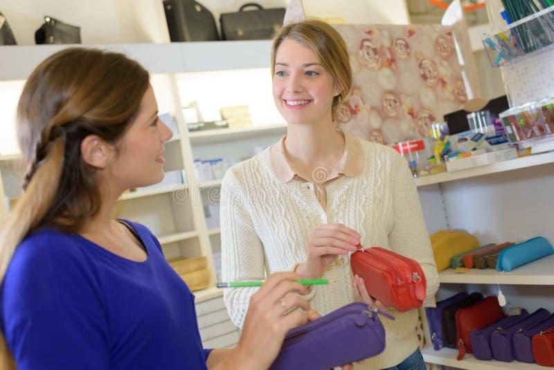 Χαμογελώντας γυναίκες που ψωνίζουν στο στάσιμο κατάστημα στοκ εικόνες