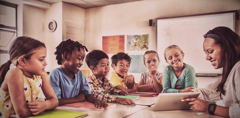 Χαμογελώντας δάσκαλος που δίνει το μάθημα με τον υπολογιστή ταμπλετών στους σπουδαστές στοκ εικόνες