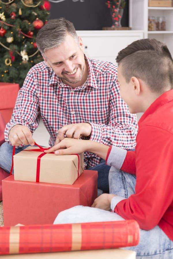 Χαμογελώντας δώρο Χριστουγέννων πατέρων ανοίγοντας στοκ φωτογραφίες