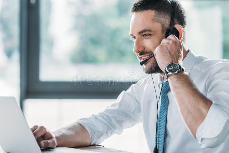 χαμογελώντας ενήλικος άμεσος εργαζόμενος υποστήριξης με το lap-top στοκ εικόνες