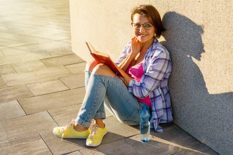 Χαμογελώντας ενήλικο θηλυκό πόσιμο νερό και ανάγνωση ενός βιβλίου στοκ εικόνες