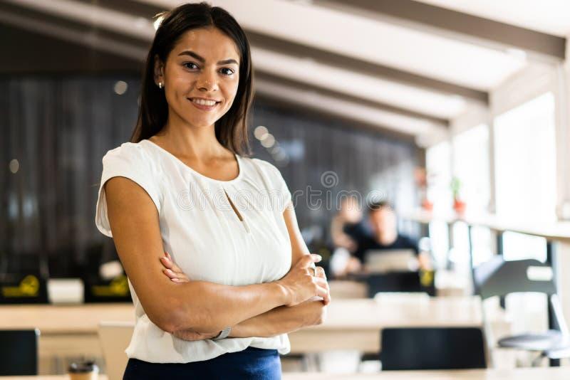Χαμογελώντας επαγγελματική επιχειρηματίας σε περιστασιακό, με τα όπλα που διασχίζονται στάση στην αρχή στοκ εικόνες