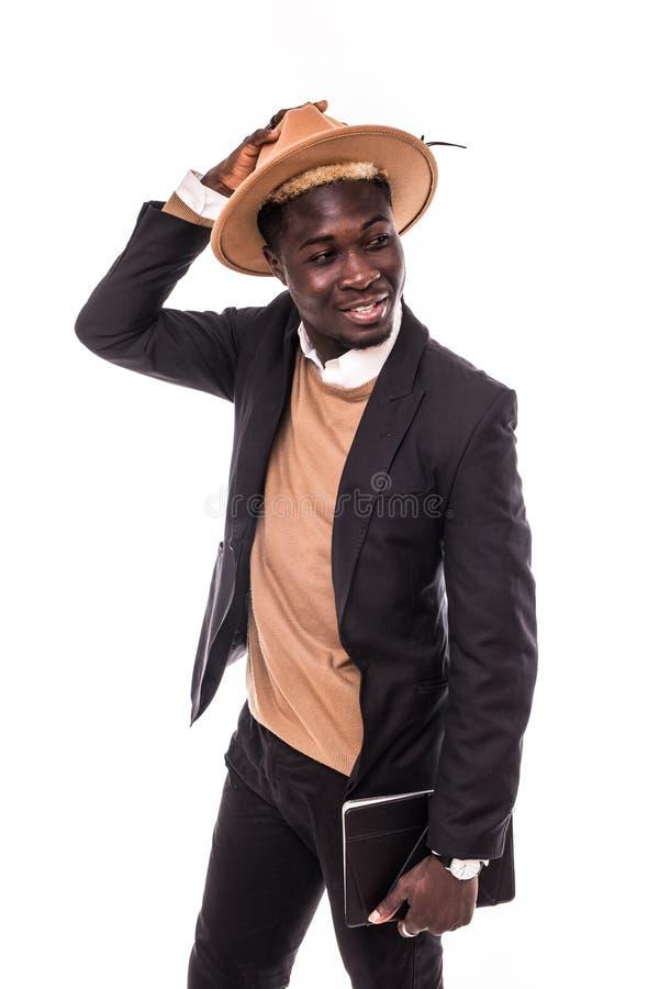 Χαμογελώντας επιχειρηματίας αφροαμερικάνων που χρησιμοποιεί την ταμπλέτα που φορά στο κοστούμι και το καπέλο Νεαρός άνδρας στο κο στοκ φωτογραφία