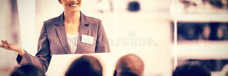 Χαμογελώντας επιχειρηματίας που ενώ οι συνάδελφοί της την προσέχουν στοκ εικόνες