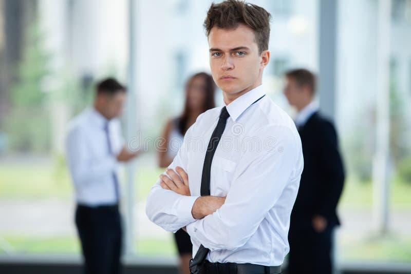 Χαμογελώντας επιχειρηματίας που θέτει μιλώντας συναδέλφων μαζί στην αρχή στοκ φωτογραφία
