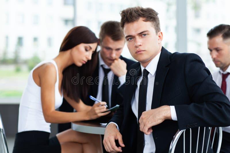 Χαμογελώντας επιχειρηματίας που θέτει μιλώντας συναδέλφων μαζί στην αρχή στοκ φωτογραφίες