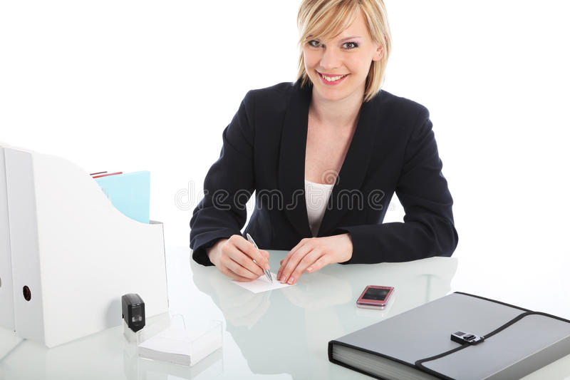 Χαμογελώντας επιχειρηματίας που κάθεται σε ένα γραφείο στοκ φωτογραφίες