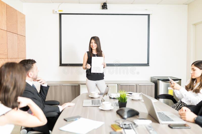 Χαμογελώντας επιχειρηματίας που παρουσιάζει έγγραφο στους διοργανωτές στοκ φωτογραφία με δικαίωμα ελεύθερης χρήσης