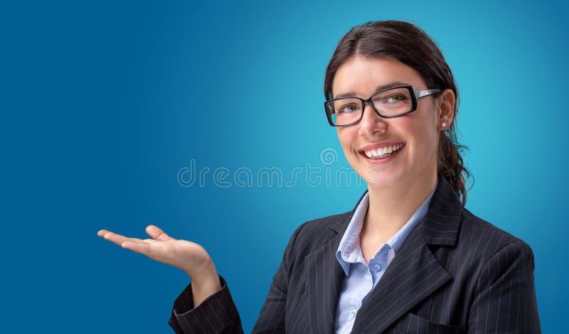 Χαμογελώντας επιχειρηματίας που παρουσιάζει κενό χέρι στοκ εικόνα