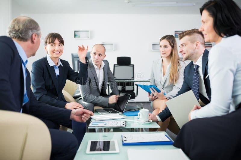Χαμογελώντας επιχειρηματίας που συζητά με τους συναδέλφους στην αρχή στοκ φωτογραφίες