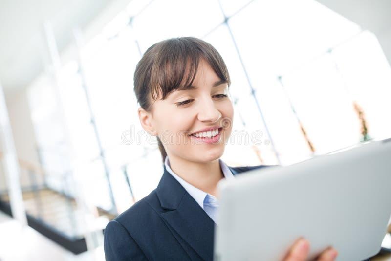 Χαμογελώντας επιχειρηματίας που χρησιμοποιεί την ψηφιακή ταμπλέτα στην αρχή στοκ φωτογραφία με δικαίωμα ελεύθερης χρήσης