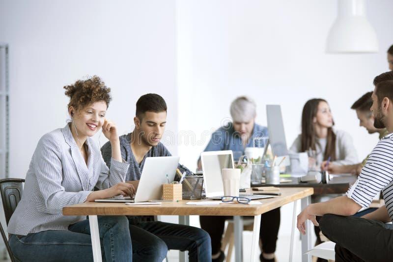 Χαμογελώντας επιχειρηματίας που χρησιμοποιεί το lap-top στοκ φωτογραφίες