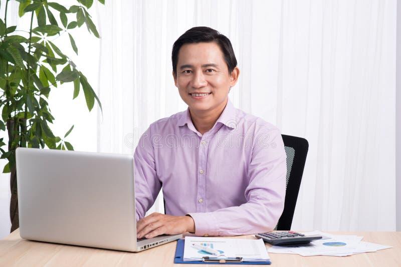 Χαμογελώντας επιχειρηματίας στο γραφείο του με το lap-top και έγγραφα σε δικοί του στοκ φωτογραφία με δικαίωμα ελεύθερης χρήσης