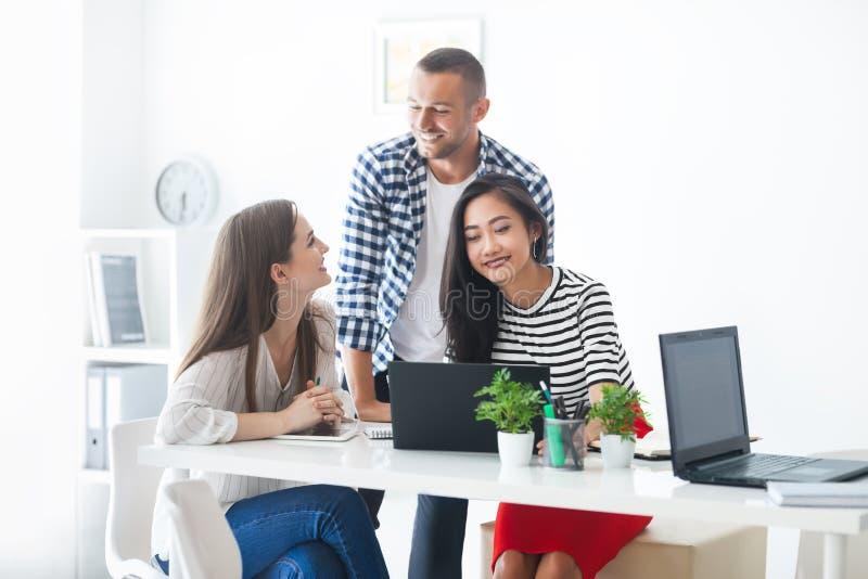 Χαμογελώντας επιχειρηματίες που μοιράζονται τις ιδέες τους στο σύγχρονο γραφείο στοκ εικόνες