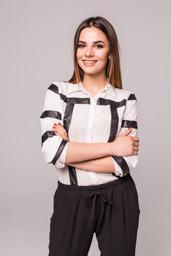 Χαμογελώντας επιχειρησιακή γυναίκα με τα διασχισμένα όπλα που στέκονται στο γκρίζο απομονωμένο στούντιο κλίμα στοκ φωτογραφία