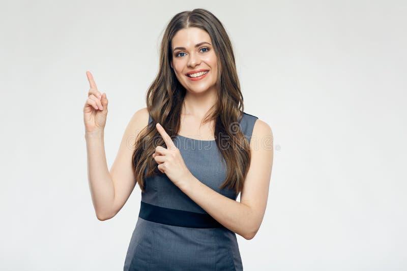 Χαμογελώντας επιχειρησιακή γυναίκα που δείχνει το δάχτυλο επάνω στοκ εικόνες
