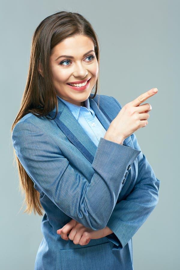 Χαμογελώντας επιχειρησιακή γυναίκα που δείχνει το δάχτυλο στο διάστημα αντιγράφων στοκ εικόνες
