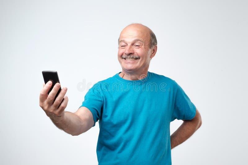 Χαμογελώντας ευτυχές ανώτερο άτομο με το mustache που παίρνει ένα selfie με το τηλέφωνό του και την αποστολή του στην οικογένειά  στοκ φωτογραφία με δικαίωμα ελεύθερης χρήσης