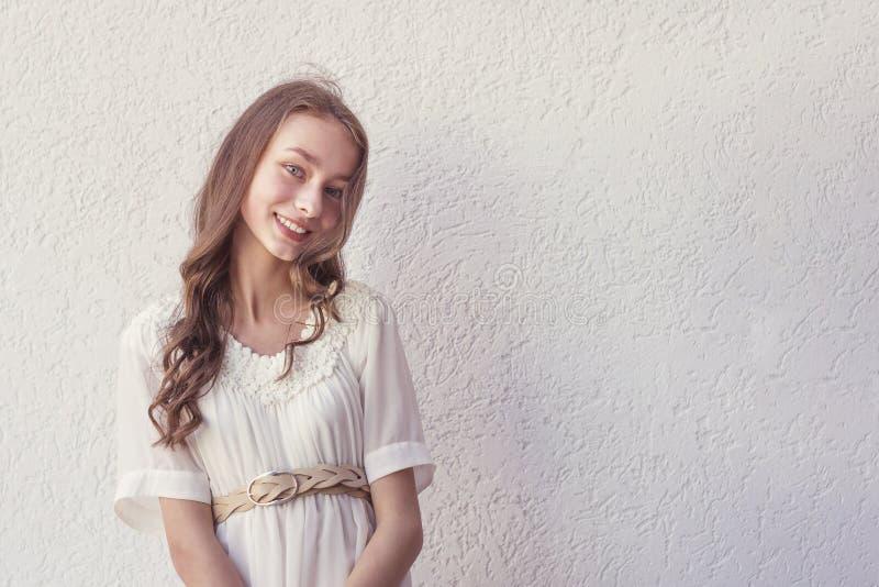 Χαμογελώντας ευτυχής γυναίκα στο άσπρο φόρεμα στοκ εικόνα