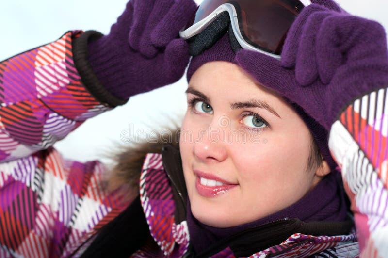 Χαμογελώντας ευτυχής νέα γυναίκα που φορά τα προστατευτικά δίοπτρα σκι στοκ φωτογραφία