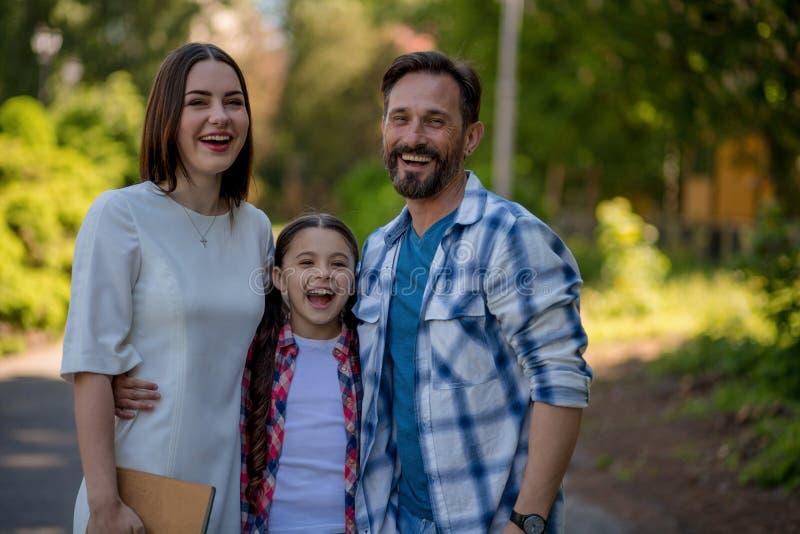 Χαμογελώντας ευτυχής οικογένεια στο πάρκο Πατέρας και κόρη μητέρων στα περιστασιακά ενδύματα Η κόρη αγκαλιάζει τους γονείς της στοκ εικόνα