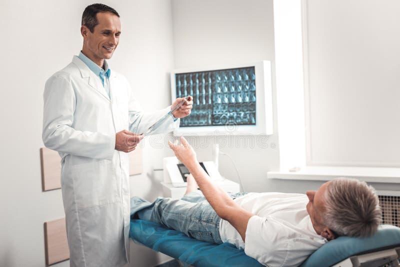 Χαμογελώντας εύθυμος γιατρός που δίνει τα αποτελέσματα της ακτίνας X στοκ εικόνα με δικαίωμα ελεύθερης χρήσης
