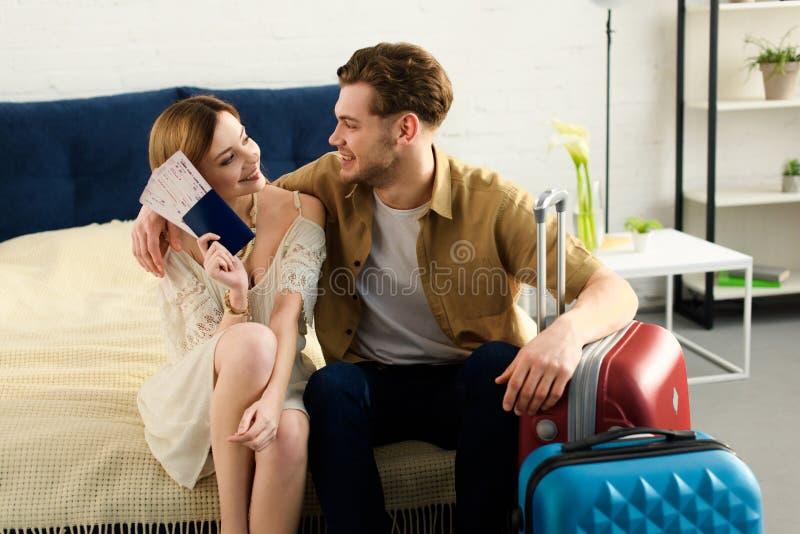 χαμογελώντας ζεύγος με τις βαλίτσες στο κρεβάτι και το κράτημα των εισιτηρίων στοκ εικόνα