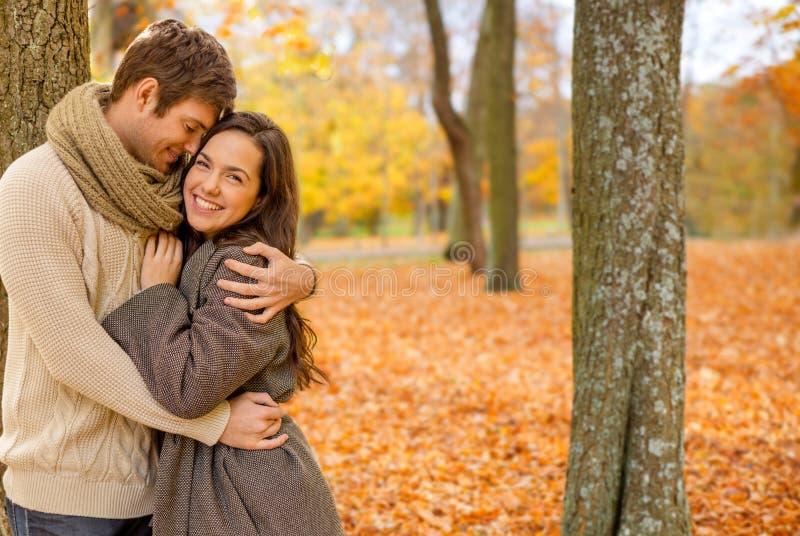 Χαμογελώντας ζεύγος που αγκαλιάζει στο πάρκο φθινοπώρου στοκ εικόνα