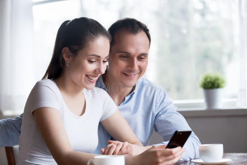 Χαμογελώντας ζεύγος που διαβάζει το αστείο μήνυμα στο τηλέφωνο στο σπ στοκ εικόνα