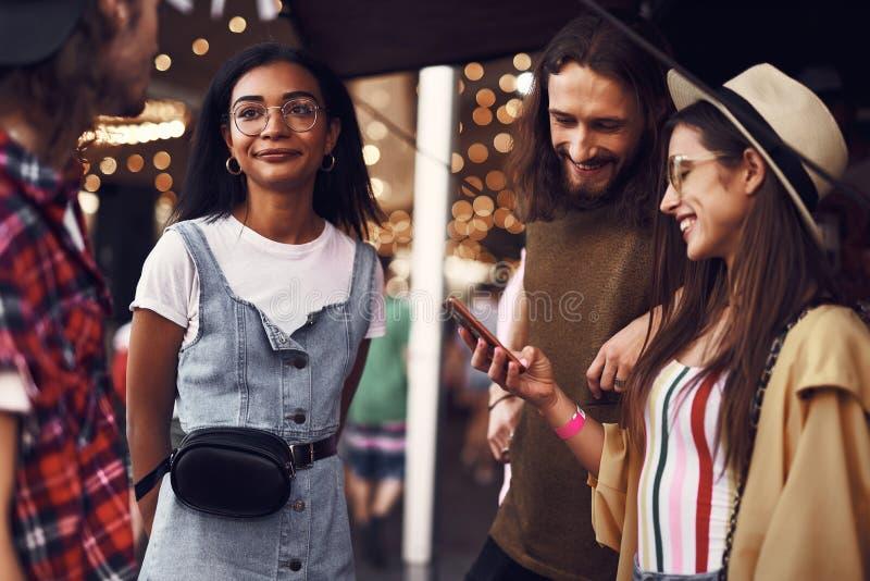 Χαμογελώντας ζεύγος που εξετάζει το smartphone η ομιλία φίλων τους στοκ φωτογραφία με δικαίωμα ελεύθερης χρήσης