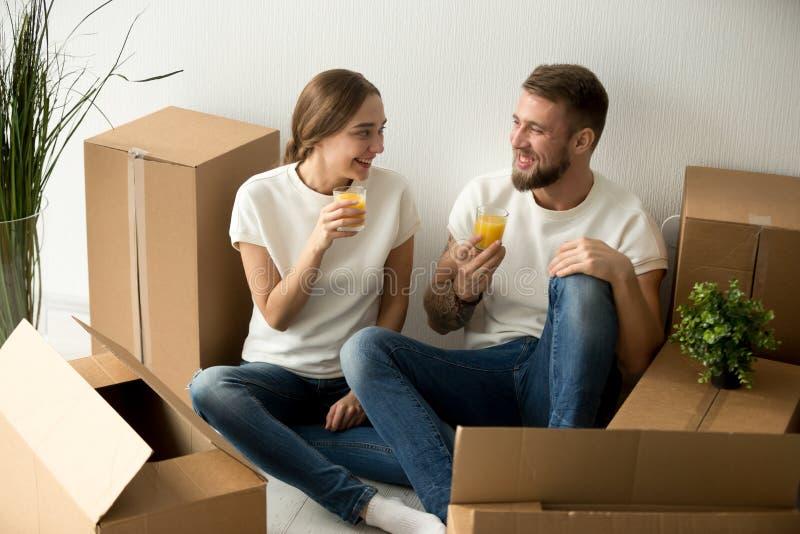 Χαμογελώντας ζεύγος που κινείται στο νέο σπίτι που έχει το χυμό κατανάλωσης σπασιμάτων στοκ εικόνες με δικαίωμα ελεύθερης χρήσης