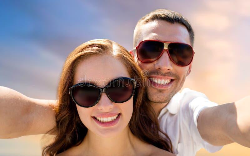 Χαμογελώντας ζεύγος που φορά τα γυαλιά ηλίου που κάνουν selfie στοκ φωτογραφίες