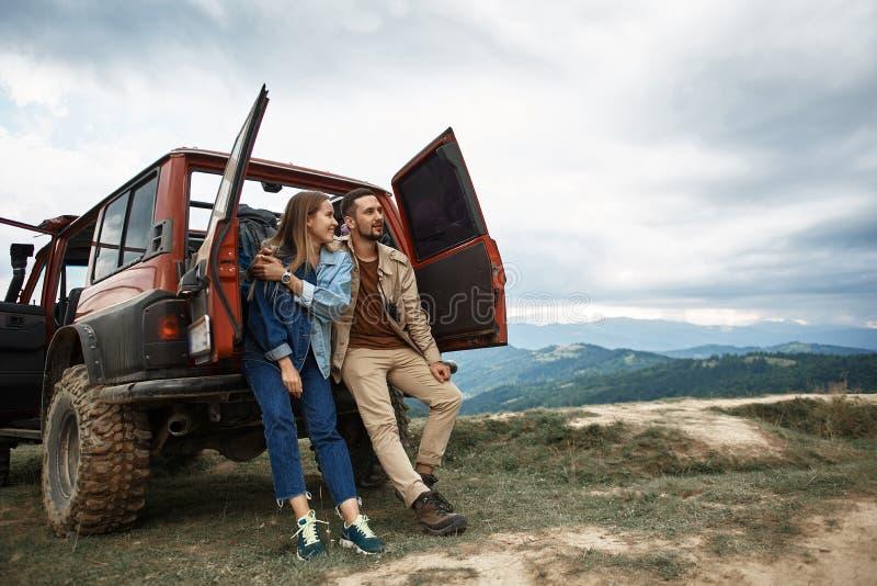 Χαμογελώντας ζεύγος της Νίκαιας που απολαμβάνει το όμορφο τοπίο βουνών στοκ εικόνες