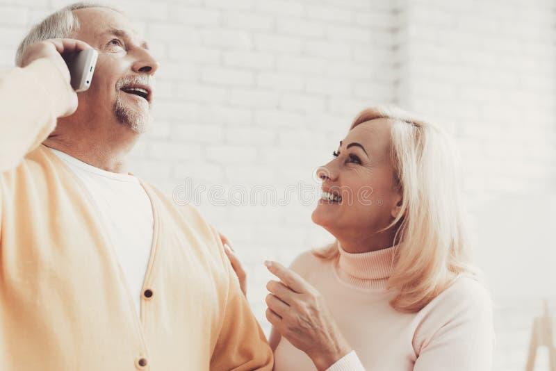 Χαμογελώντας ηληκιωμένος και γυναίκα που μιλούν σε Smartphone στοκ εικόνες