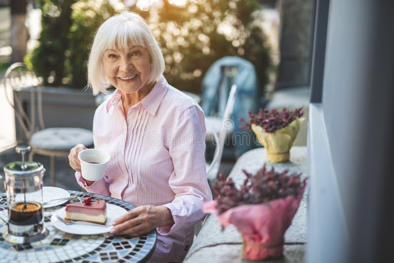 Χαμογελώντας ηλικιωμένη γυναίκα που απολαμβάνει το τσάι υπαίθρια στοκ φωτογραφίες