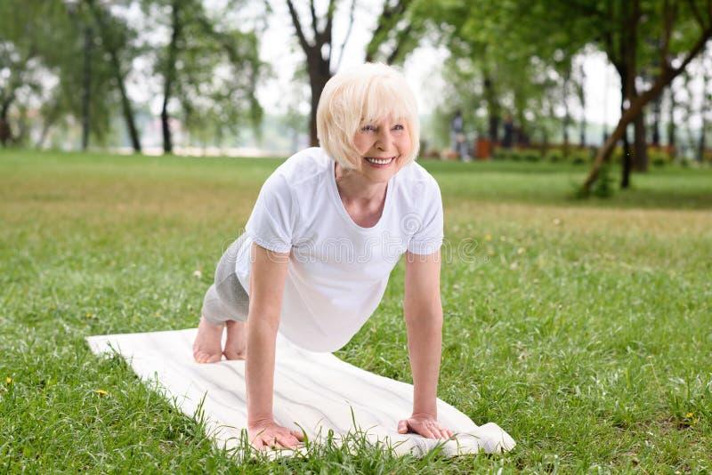 χαμογελώντας ηλικιωμένη γυναίκα που κάνει τη σανίδα στο χαλί γιόγκας στοκ εικόνες