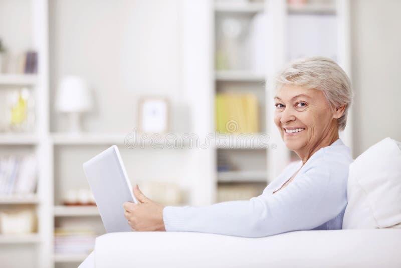 Χαμογελώντας ηλικιωμένη γυναίκα στο σπίτι στοκ εικόνες με δικαίωμα ελεύθερης χρήσης