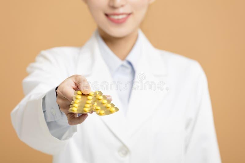 Χαμογελώντας θηλυκός γιατρός που δίνει τα χάπια στοκ φωτογραφία