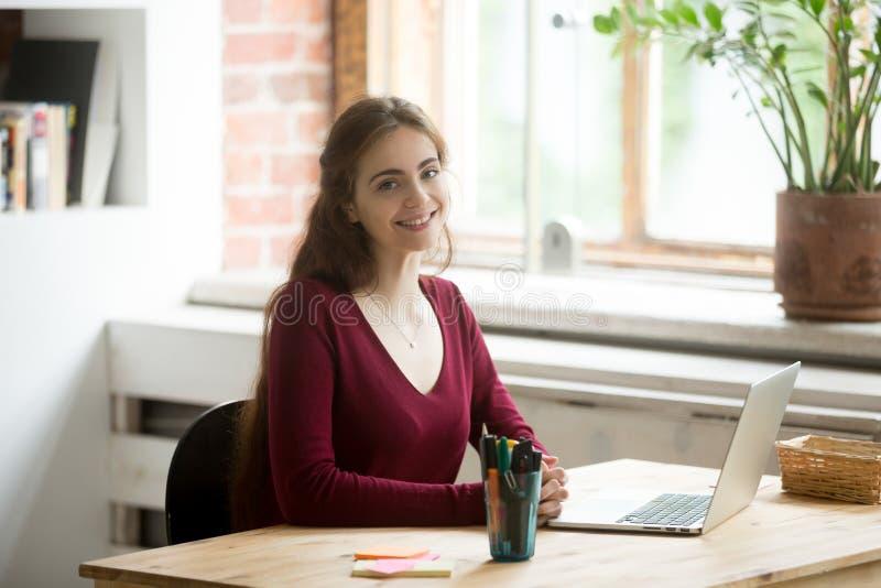 Χαμογελώντας θηλυκό που θέτει εργαζόμενο στο lap-top στοκ φωτογραφία με δικαίωμα ελεύθερης χρήσης